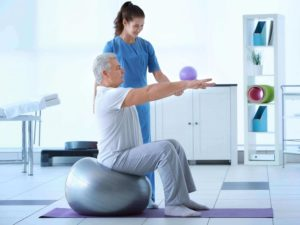 Elder man doing exercise with the help young woman nurse
